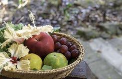 Apple, Sinaasappel en druif in de manden van het weefselbamboe met bloemendecoratie onscherpe bomen Als achtergrond stock foto