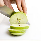 Apple sliced. Sliced green apple in multiple peices with knife royalty free stock photography