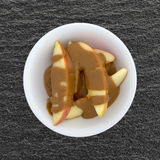 Apple slices covered with peanut butter on a table Royalty Free Stock Image