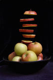Apple Slices. Sliced apple floating above a bowl of apples Stock Photos