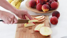 Apple slices. Woman slicing apple on a wooden cutting board, close up, on white background. Woman slicing apple on a wooden cutting board stock video