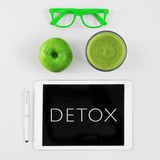 Apple, smoothie, eyeglasses and word detox in a tablet computer Stock Photos