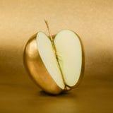 Apple snitt med den guld- peelen på guld- bakgrund Arkivfoton