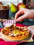 Apple som är syrlig med pärondriftstopp, häller karamell, händer Arkivbild