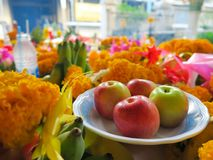 Apple and some marigold for worship. To holy thing according to belief of buddhist in Thailnad Royalty Free Stock Photos