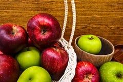Apple sont dans le panier et sur la table en bois image stock