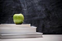 Apple sopra i libri con la lavagna Fotografia Stock