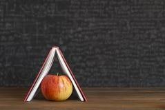 Apple sous des livres, maison photo libre de droits
