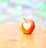Apple sous forme de coeur sur un fond en bois Image libre de droits