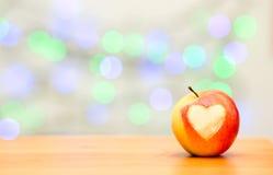 Apple sous forme de coeur sur un fond en bois Photos stock