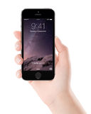 Apple Space Gray iPhone 5S with lock screen on the display in fe Royalty Free Stock Photos