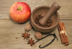 Apple and spice. Apple pestle and mortar and spices,cinnamon,vanilla,nutmeg and star anise on rustic wood Royalty Free Stock Photo