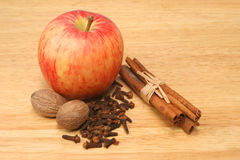 Apple and spices. Nutmeg,cloves and cinnamon on a wooden board Royalty Free Stock Images