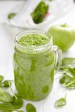 Apple and spinach smoothie in glass on a wooden Stock Photography