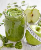 Apple and spinach smoothie in glass on a wooden Royalty Free Stock Photo