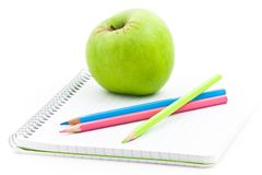 Apple and spiral notebook. Spiral notebook, colorful pencils, and, apple for afternoon Stock Photos