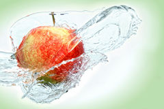 Apple splash. Watering apple with water stock images