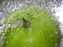 Apple splash. Water splashing onto an apple stock images