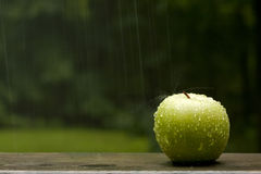 Apple Splashed by Rain. A still life of a green apple outdoors in the rain with droplets and splash on apple Royalty Free Stock Photos