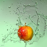 Apple with splashes of water Royalty Free Stock Images