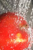 Apple splashing water. Fresh water splashing on apple Stock Images