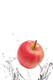 Apple splashing in water. Ripe red apple splashing in water, isolated on white background royalty free stock image