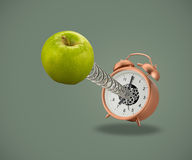 Apple on spring coming out of alarm clock Royalty Free Stock Image