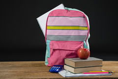 Apple on stack of books with calculator and school bag. Apple on stack of books with calculator and bag on table Royalty Free Stock Image
