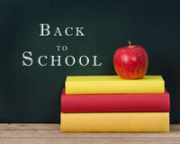 Apple on the stack of books chalkboard background Stock Photography