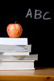 Apple on stack of books in classroom Royalty Free Stock Photos