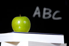 Apple on stack of books in classroom Stock Photography