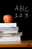 Apple on stack of books in classroom Royalty Free Stock Images