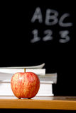Apple and stack of books in classroom Royalty Free Stock Photo