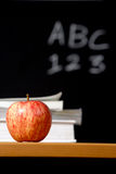 Apple on stack of books in classroom Stock Photos