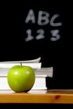 Apple and stack of books in classroom Stock Image