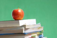 Apple on stack of books in classroom Stock Image