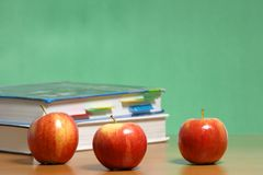Apple on stack of books in classroom royalty free stock photography