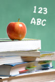Apple on stack of books in classroom Stock Photo