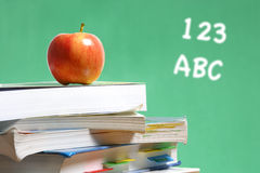 Apple on stack of books in classroom Royalty Free Stock Photo