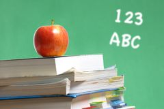 Apple on stack of books in classroom Royalty Free Stock Image