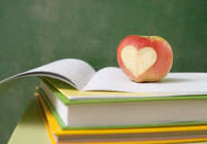 Apple on stack of books next to a chalk Board Stock Photography