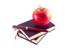 Apple on stack of books with pen Stock Photo