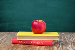 Apple on stack books wooden table blackboard background. Stock Photo