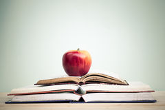 Apple on stack of open books. With copy space Royalty Free Stock Photography