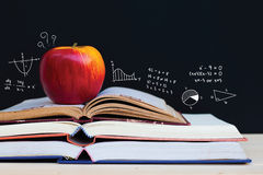 Apple on stack of open books with education doodles Stock Images