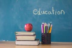 Apple stawia dalej książkowego studiowanie tło jest blackboard, edu zdjęcie stock