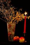 Apple, stearinljus och vas av blommor på svart bakgrund Royaltyfria Bilder