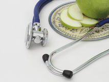 Stethoscope. Green apple and apple slices on a plate with blue stethoscope on a white background Stock Image
