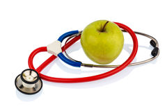 Apple and stethoscope. An apple and a stethoscope on a doctor. symbolic photo for healthy and vitamin-rich diet royalty free stock image