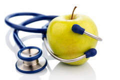 Apple and stethoscope. An apple and a stethoscope on a doctor. symbolic photo for healthy and vitamin-rich diet Stock Images